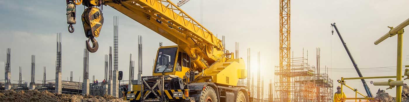 Yellow rough terrain crane on a construction yard, with worker, all terrain and tower cranes in the background.